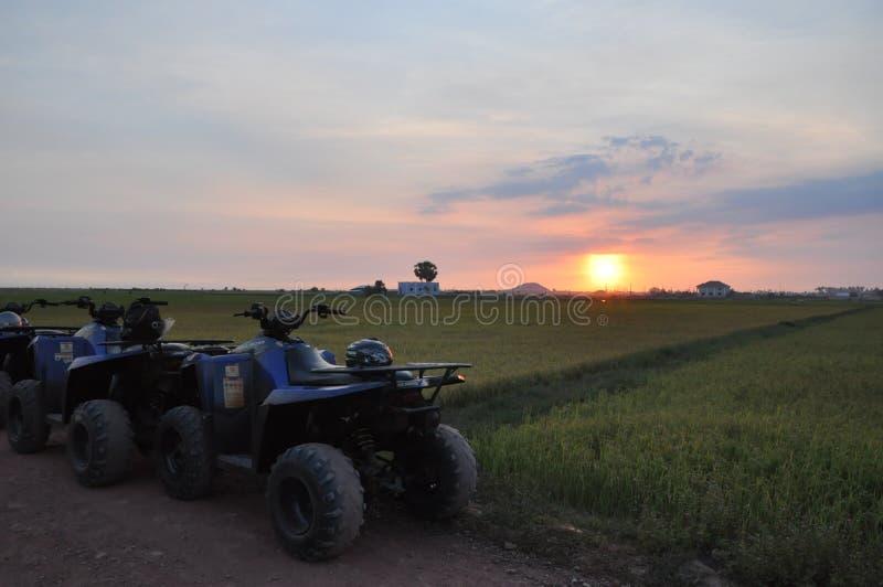 Opinión de la puesta del sol con la moto de cuatro ruedas imágenes de archivo libres de regalías