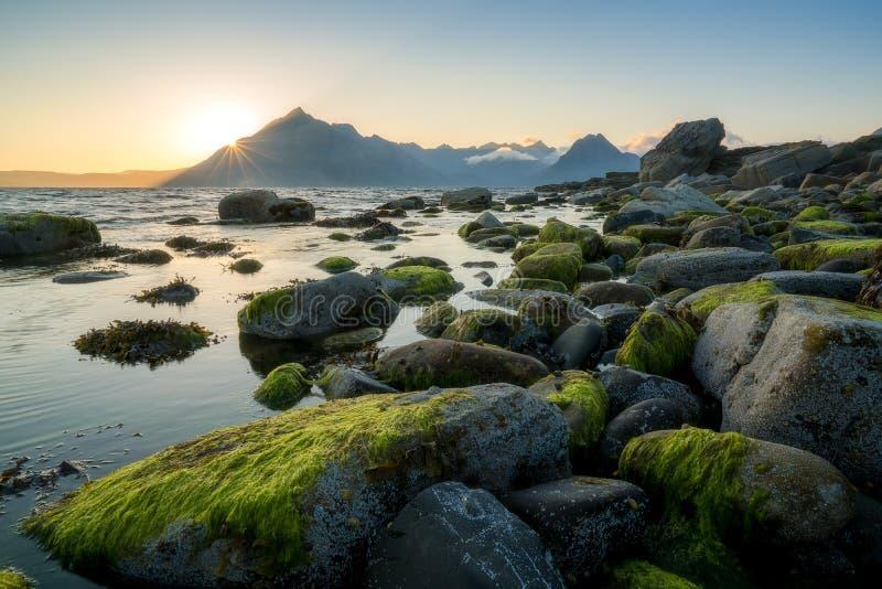 Opinión de la puesta del sol de las montañas negras de Cuillin de la playa rocosa de Elgol foto de archivo libre de regalías
