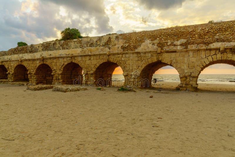 Opinión de la puesta del sol la playa y Roman Aqueduct en Caesarea fotografía de archivo libre de regalías
