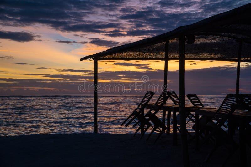 Opinión de la puesta del sol sobre un restaurante cerrado de la playa al final de la estación imagen de archivo