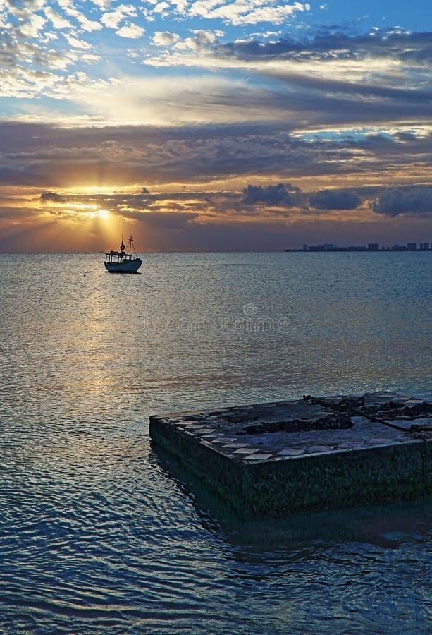 Opinión de la salida del sol del barco de pesca mexicano en Puerto Juarez Cancun México foto de archivo