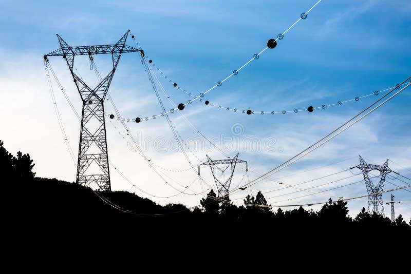 Opinión de la silueta de pasar las torres de cables eléctricos de alto voltaje foto de archivo libre de regalías