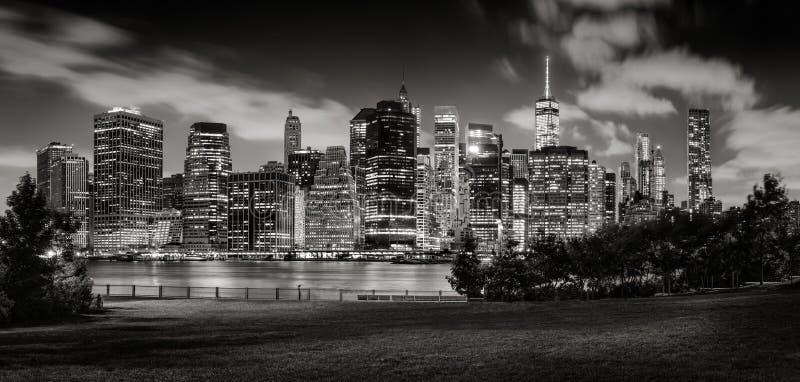 Opinión de la tarde de los rascacielos del Lower Manhattan a través del parque del puente de Brooklyn en negro y blanco imagenes de archivo