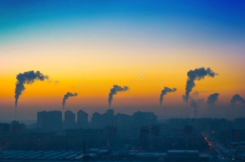 Opinión de la tarde del paisaje industrial de la ciudad con las emisiones de humo de las chimeneas en la puesta del sol imagen de archivo