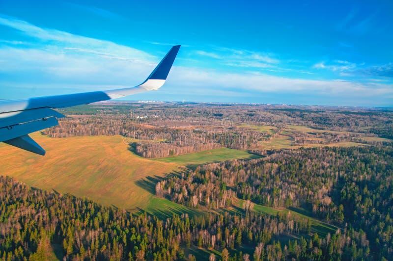Opinión de la ventana del aeroplano Visión desde la ventana en el bosque de la primavera, prados, cielo azul Vuelo del ala del `  imagenes de archivo