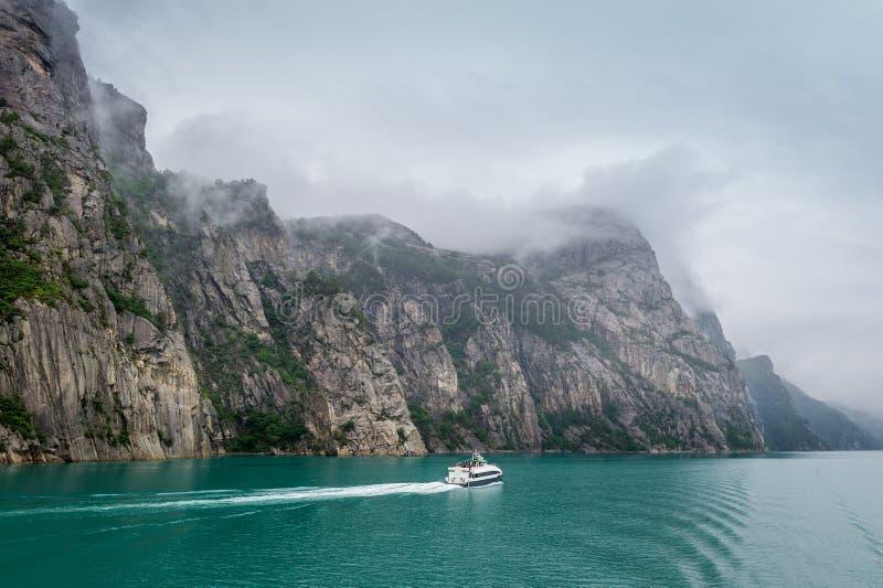Opinión de Lysefjord del noruego con el pequeño transbordador imagenes de archivo