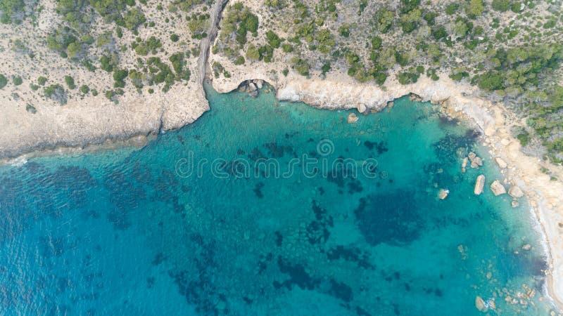 Opinión de ojo de pájaros de aguas azules transparentes con los arrecifes de coral y los acantilados en la isla tropical fotos de archivo