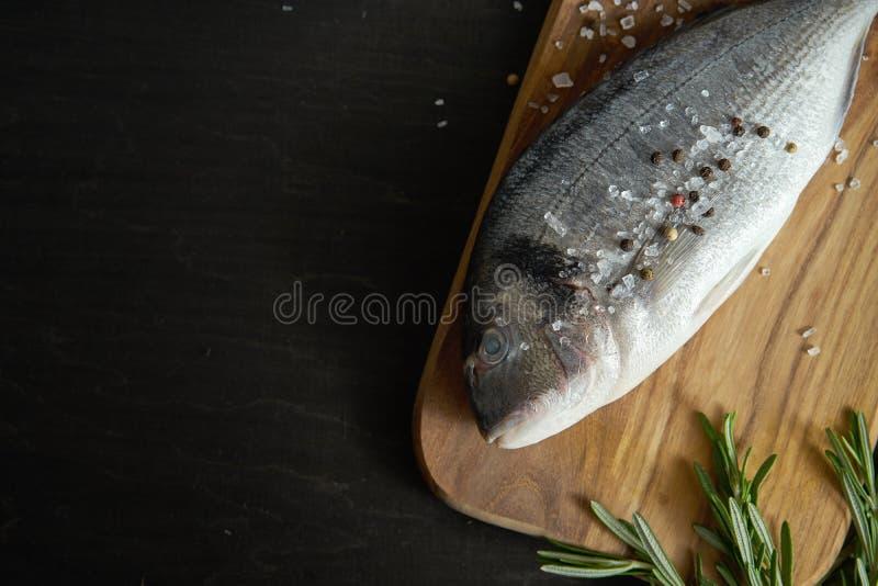 Opinión de Op. Sys. los pescados crudos frescos del dorada con romero, pimienta y sal en un tablero de madera y una tabla negra imagen de archivo libre de regalías