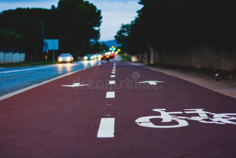 Opinión de perspectiva del carril de la bici cerca de la calle con los coches y las luces borrosos fotografía de archivo libre de regalías
