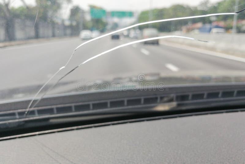 Opinión de perspectiva del parabrisas o del parabrisas agrietado del coche mientras que d imagen de archivo libre de regalías