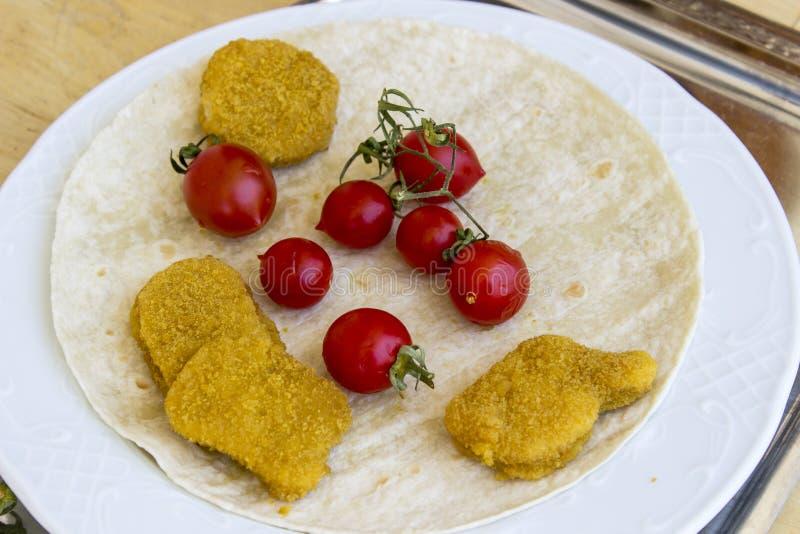 Opinión de perspectiva de las pepitas de pollo y de los pequeños tomates frescos rojos en la placa blanca ancha como desayuno fotografía de archivo