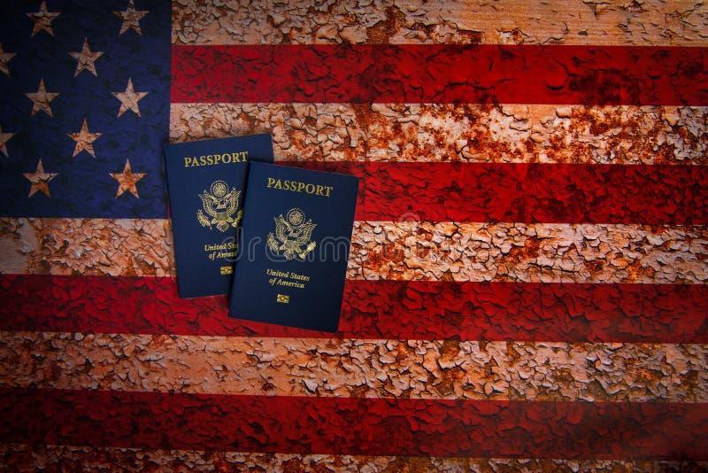 Opinión de Pverhead de dos pasaportes de los E.E.U.U. en un fondo rústico de la bandera americana imágenes de archivo libres de regalías