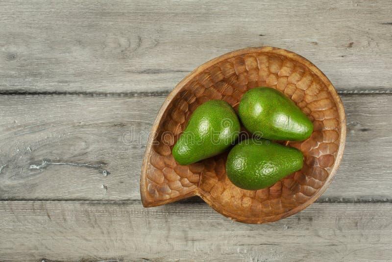 Opinión de sobremesa, tres aguacates enteros en lugar tallado de madera del cuenco fotografía de archivo