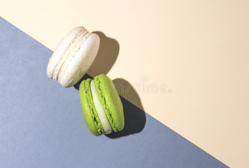 Opinión de top beige gris de la sombra del fondo de la vainilla verde de dos macarrones foto de archivo libre de regalías