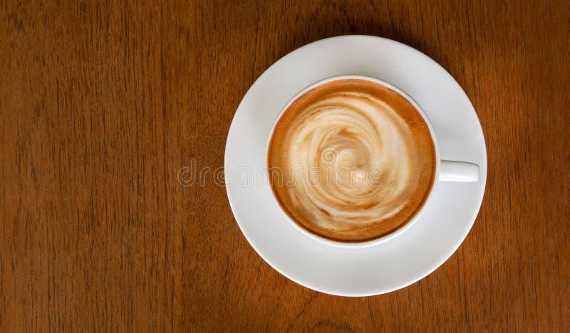 Opini?n de top espiral de la espuma de la leche del caf? del latte caliente del capuchino sobre fondo de madera fotos de archivo libres de regalías