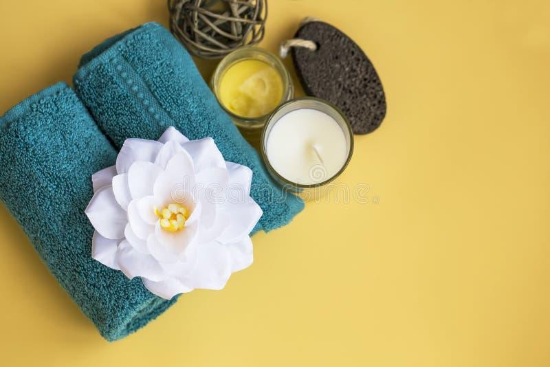 Opinión de top de la vida de la calma del balneario con la flor, la toalla y la vela del lirio de agua en fondo amarillo fotografía de archivo
