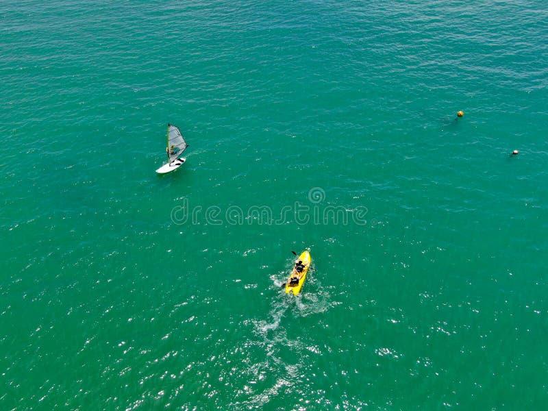 Opinión de visión aérea los hombres activos jovenes fuertes kayaking en el agua azul clara de la turquesa del océano imagen de archivo libre de regalías