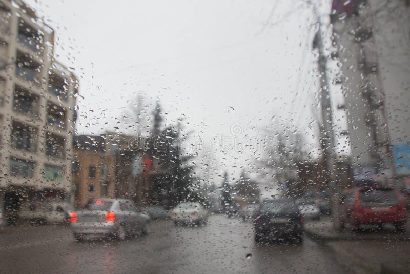Opinión del camino a través de la ventanilla del coche con gotas de lluvia Luces de Bokeh de la calle desenfocado imagen de archivo libre de regalías