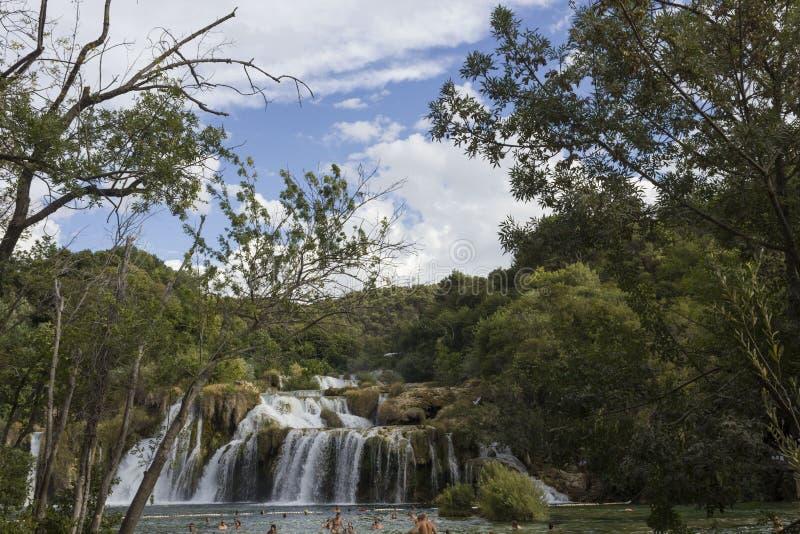 Opinión del día de las cascadas de Krka en el parque natual, con la gente bañándose en el lago fotografía de archivo