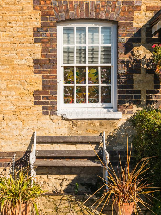 Opinión del día soleado de la ventana blanca vieja en la pared de ladrillo vieja y del banco en Inglaterra imágenes de archivo libres de regalías