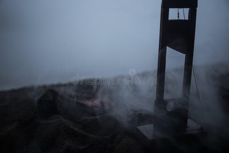 Opinión del horror de la guillotina Primer de una guillotina en un fondo de niebla oscuro imagenes de archivo