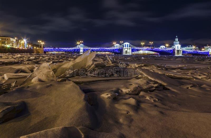 Opinión del invierno del puente adornado del palacio en St Petersburg El puente iluminado del palacio sobre el río congelado de N imágenes de archivo libres de regalías