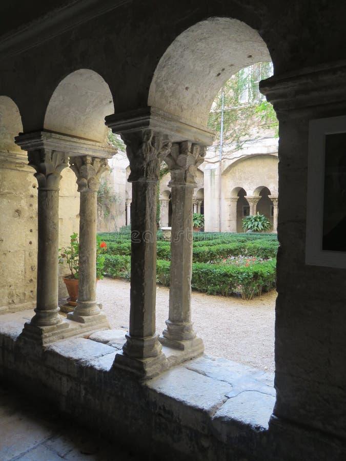 Opinión del jardín a través de arcos acolumnados franceses antiguos imagen de archivo libre de regalías