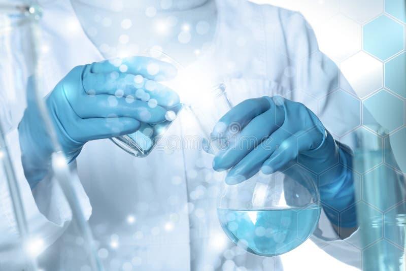 Opinión del líquido de colada del color del científico del cubilete en el frasco, exposición doble del primer fotografía de archivo