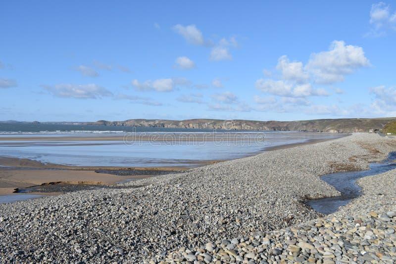 Opinión del mar de la playa con la tabla y los guijarros en primero plano y de acantilados en distancia y del mar centrado fotos de archivo