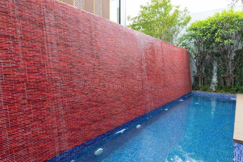 Opinión del paisaje de la piscina con la cascada de la pared de ladrillo en la casa de lujo del patio trasero exterior imágenes de archivo libres de regalías