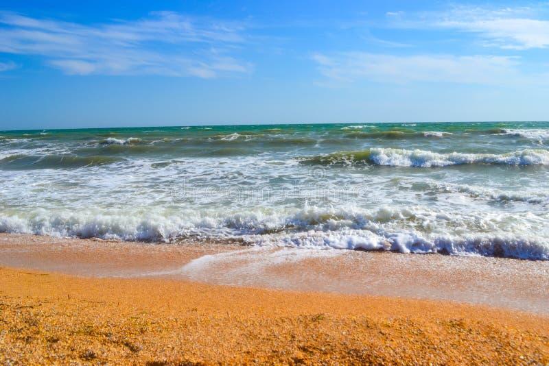 Opinión del paisaje de una costa con sol brillante y nubes azules claras fotografía de archivo libre de regalías