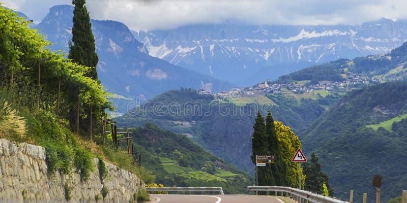 Opinión del paisaje del fondo de los campos de la uva y del pueblo alpino en la distancia entre las montañas fotografía de archivo