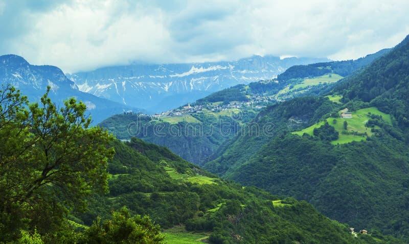 Opinión del paisaje del fondo de los campos de la uva y del pueblo alpino en la distancia entre las montañas fotos de archivo libres de regalías