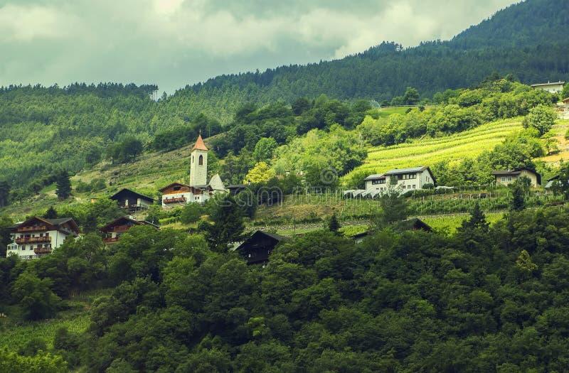 Opinión del paisaje del fondo de un pequeño pueblo alpino en el Tyrol foto de archivo
