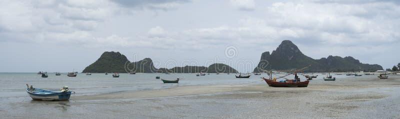 Opinión del panorama del barco de pesca tradicional que pone en una playa cerca del mar con la montaña grande y larga en el fondo imagen de archivo