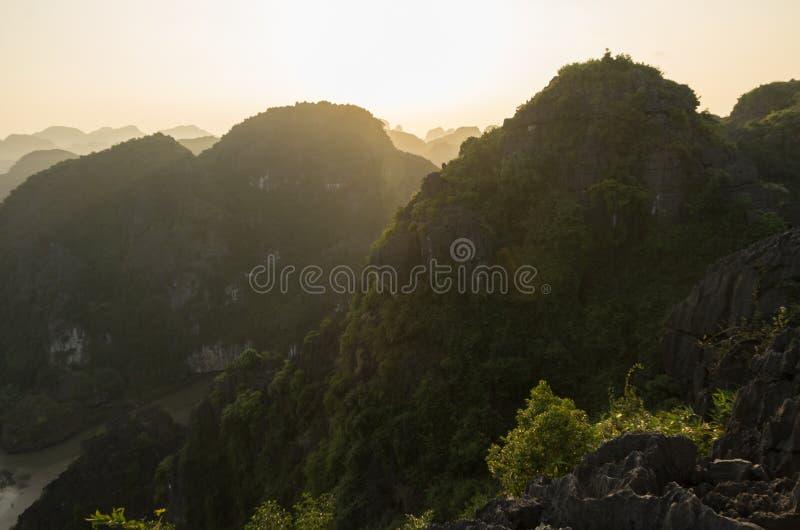 Opinión del panorama que sorprende de las rocas y de las cimas de la montaña de la piedra caliza de Hang Mua Temple en la tarde N imagen de archivo libre de regalías