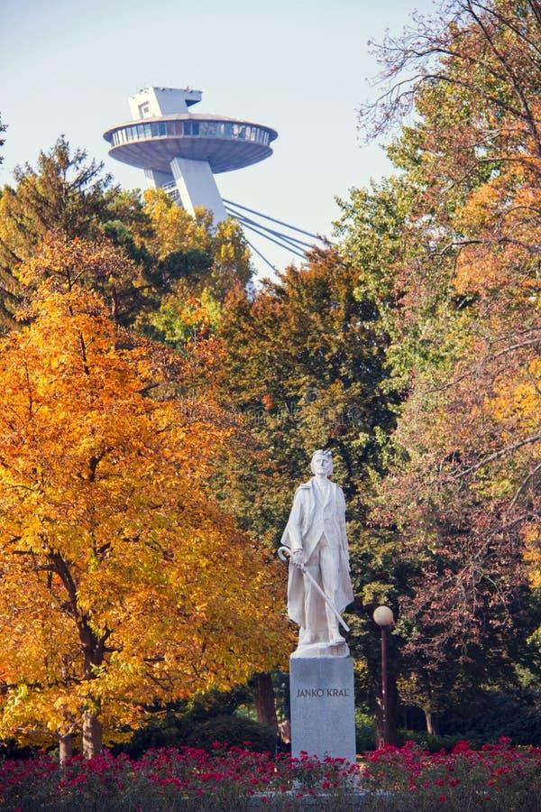 Opinión del parque de la ciudad del humor del otoño, hojas de otoño coloridas en los árboles enormes, estatua de Janko Kral y señ imágenes de archivo libres de regalías