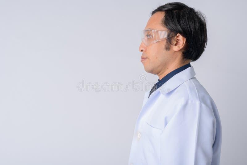 Opinión del perfil el doctor japonés del hombre que lleva los vidrios protectores imagen de archivo