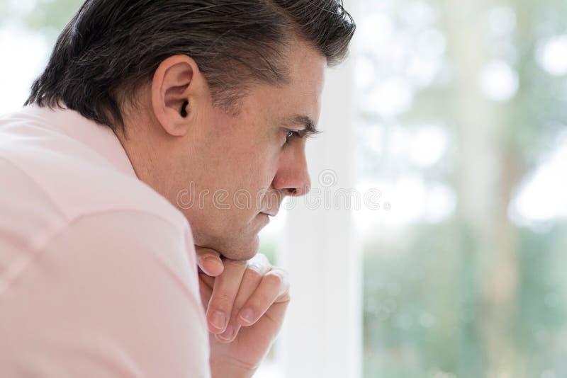 Opinión del perfil el hombre maduro preocupante en casa fotos de archivo