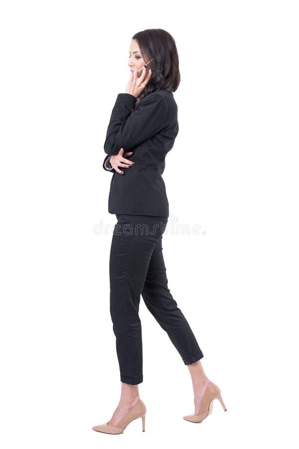 Opinión del perfil la mujer de negocios joven acertada que camina y que hace llamadas de teléfono móvil imagen de archivo