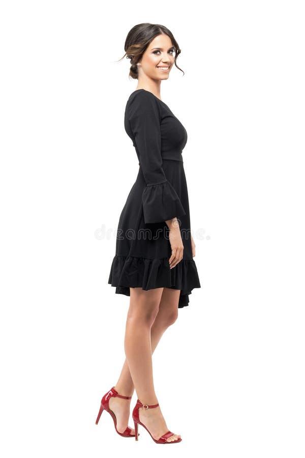 Opinión del perfil la mujer hispánica sonriente feliz en el vestido negro del volante que mira la cámara imagen de archivo libre de regalías