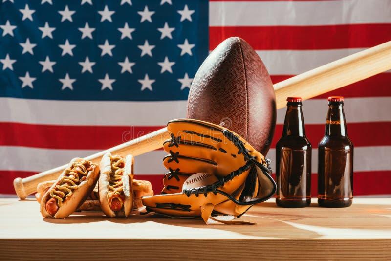 opinión del primer de la cerveza con los perritos calientes y el equipo de deporte con la bandera americana fotografía de archivo