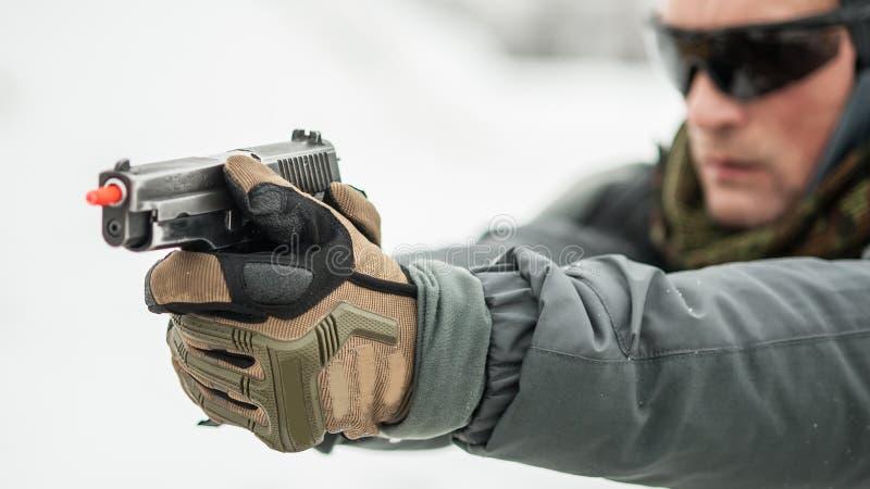 Opini?n del primer de las manos de la pistola que sostienen el arma con el palillo de la seguridad fotografía de archivo