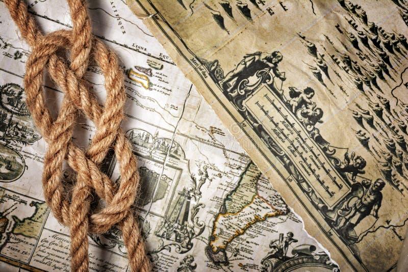 Opinión del primer de un nudo del mar de la cuerda en un mapa retro viejo fotos de archivo libres de regalías