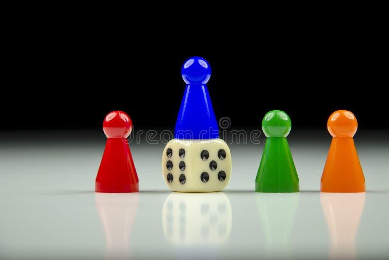 Opinión del primer de una fila de figuras y del cubo coloreados el jugar con el fondo blanco y negro borroso fotos de archivo