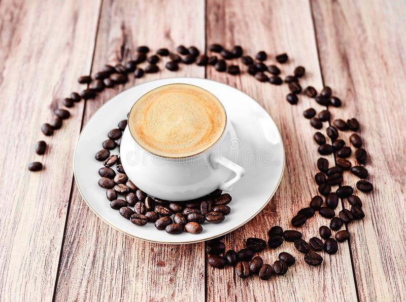 Opinión del primer de una taza de café caliente en la tabla rústica de madera con los granos de café derramados fotografía de archivo libre de regalías