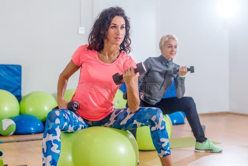 Opinión del primer del ejercicio femenino moreno joven del ajuste con las pesas de gimnasia que se sientan en bola suiza durante  imágenes de archivo libres de regalías