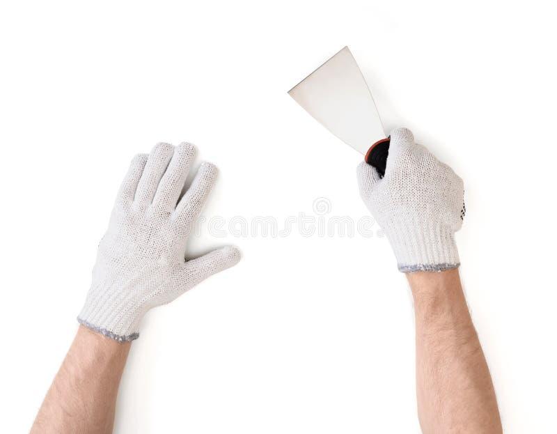 Opinión del primer del man& x27; manos de s en los guantes blancos del algodón con el cuchillo de masilla foto de archivo