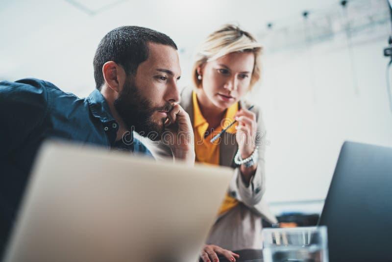 Opinión del primer dos compañeros de trabajo jovenes que trabajan en el ordenador portátil móvil en la oficina Mujer que se?ala e imagenes de archivo