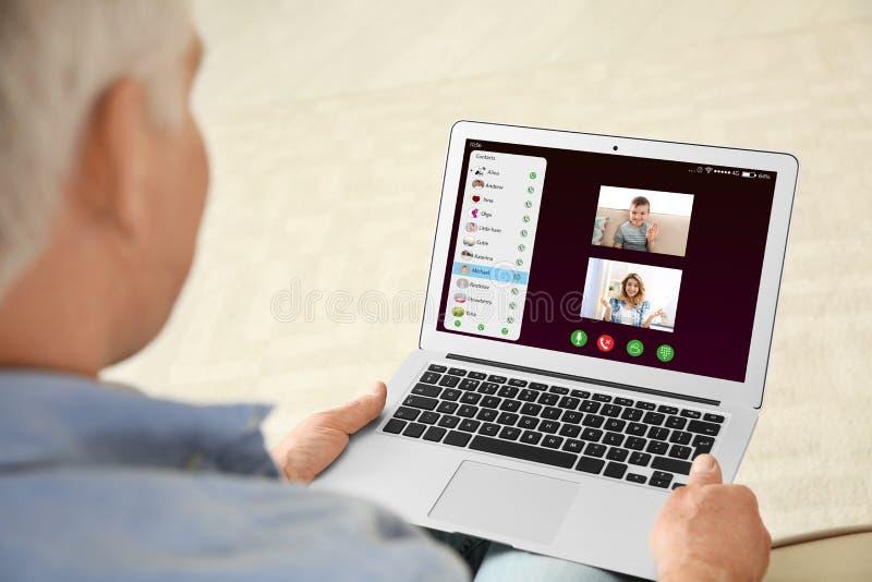 Opini?n del primer el hombre mayor que habla con los miembros de la familia v?a la charla video fotografía de archivo